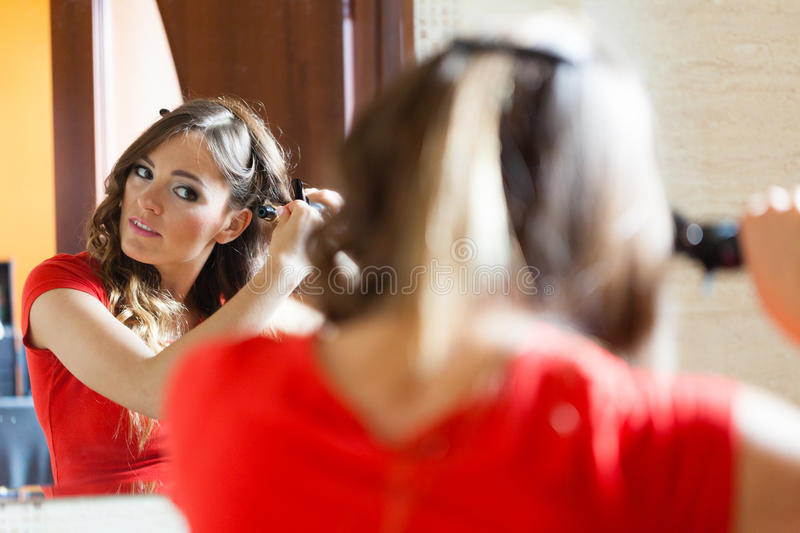 Attractive woman making hairstyle. Hairstyles concept. Gorgeous woman with elegant make up making beauty hairdo curls on long straight dark hair. Reflection in royalty free stock photo