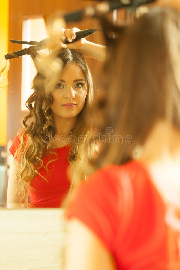 Attractive woman making hairstyle. Hairstyles concept. Gorgeous woman with elegant make up making beauty hairdo curls on long straight dark hair. Reflection in royalty free stock images