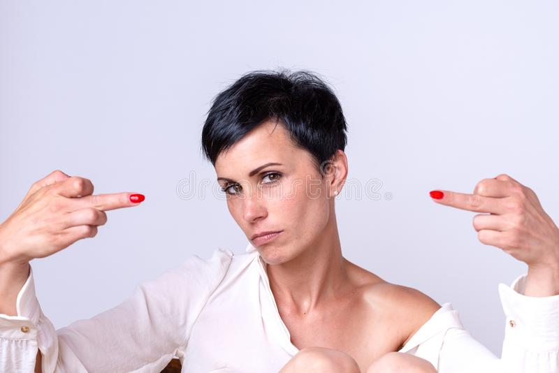 Attractive woman making a middle finger gesture. Attractive woman making a derogatory middle finger gesture with both hands pointing to herself while looking royalty free stock image