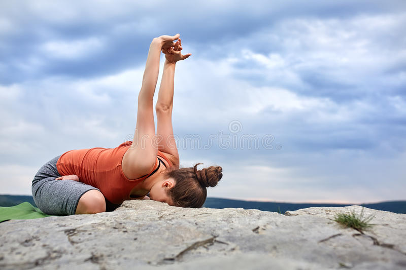 Attractive woman making yoga exercise on the big stone against beautiful river. stock images
