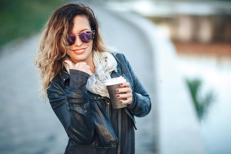 Attractive woman in mirrored sunglasses, a black leather jacket, drinking coffee on the waterfront river in the city in front the stock image