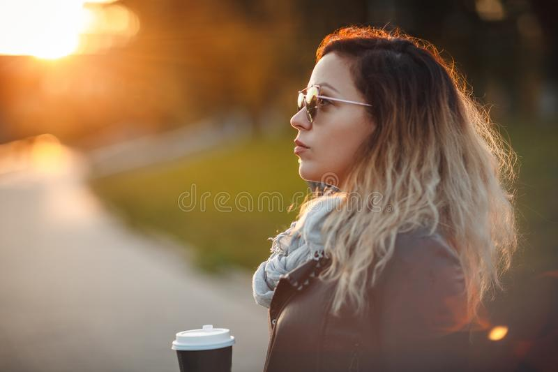 Attractive woman in mirrored sunglasses, a black leather jacket, drinking coffee on the waterfront river in the city in front the stock images