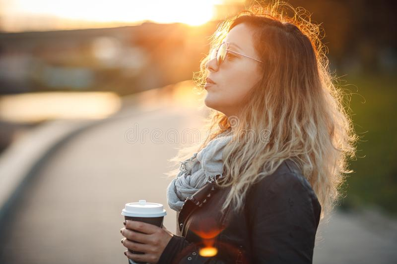 Attractive woman in mirrored sunglasses, a black leather jacket, drinking coffee on the waterfront river in the city in front the royalty free stock image