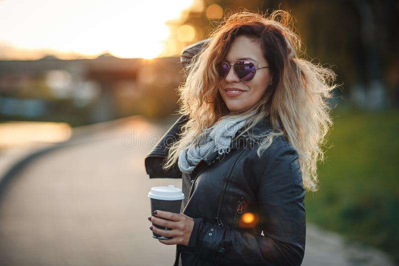 Attractive woman in mirrored sunglasses, a black leather jacket, drinking coffee on the waterfront river in the city in front the stock photo