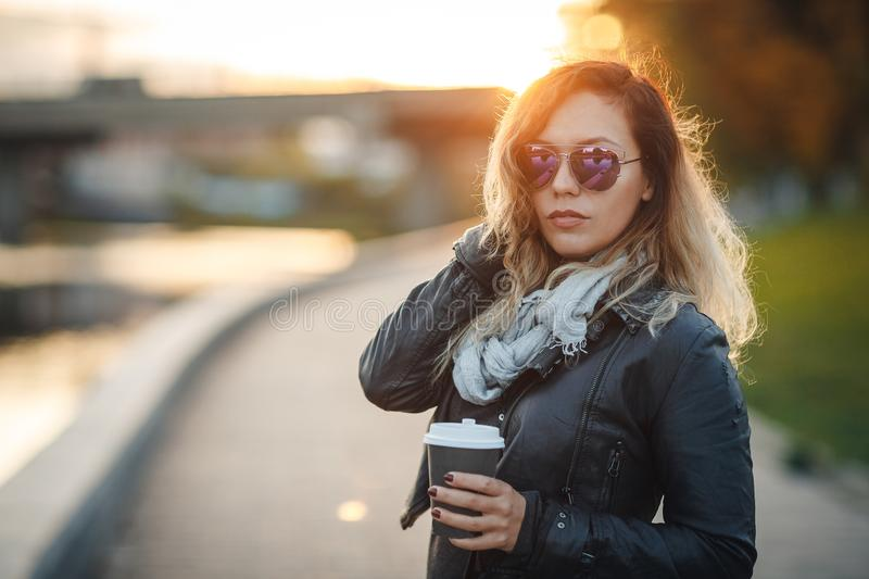 Attractive woman in mirrored sunglasses, a black leather jacket, drinking coffee on the waterfront river in the city in front the royalty free stock photo