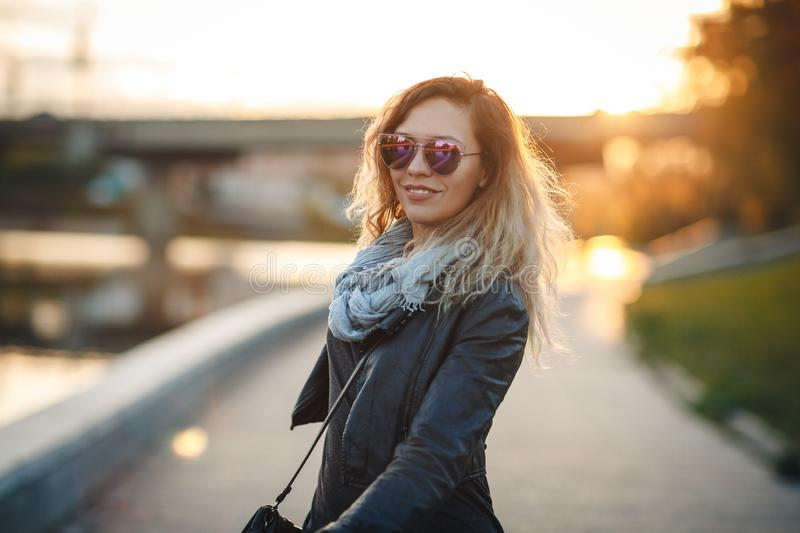 Attractive woman in mirrored sunglasses, a black leather jacket, black jeans walking along the river Bank in the city, turns to ca royalty free stock images