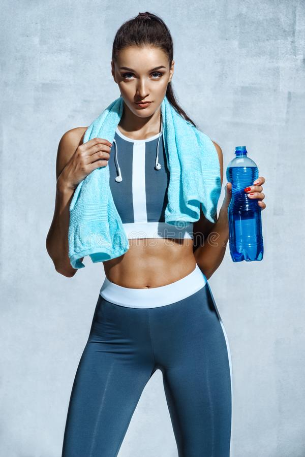 Attractive woman with muscular body holding bottle of refreshing water royalty free stock photos