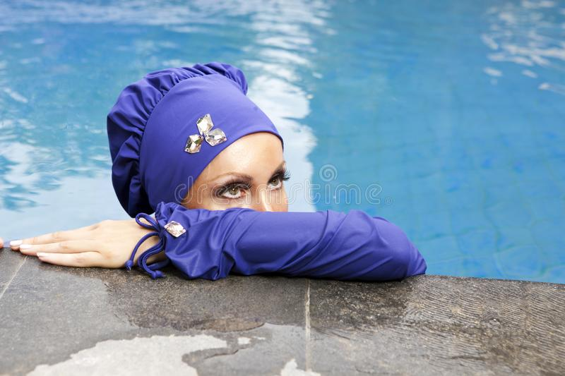Attractive woman in a Muslim swimwear burkini in the pool, a close up on eyes royalty free stock image