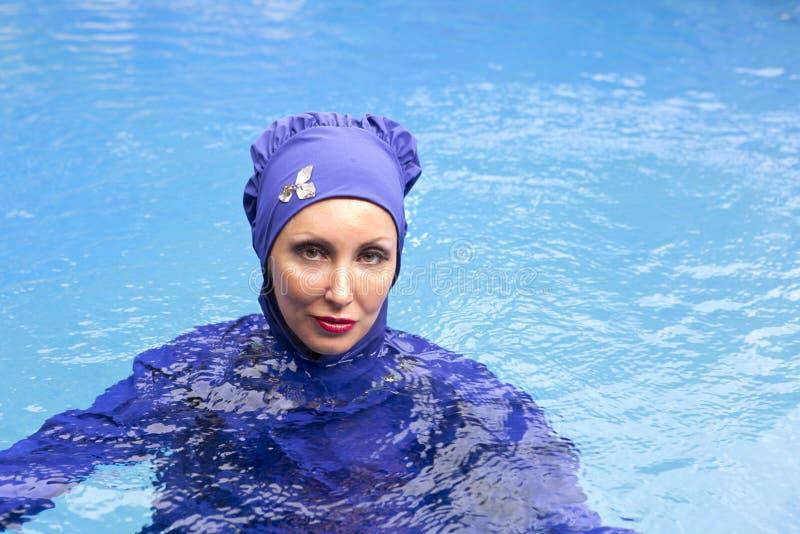 Attractive woman in a Muslim swimwear burkini in the sea stock photography