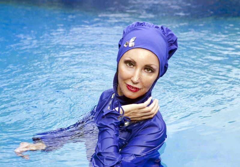 Attractive woman in a Muslim swimwear burkini in the sea stock images