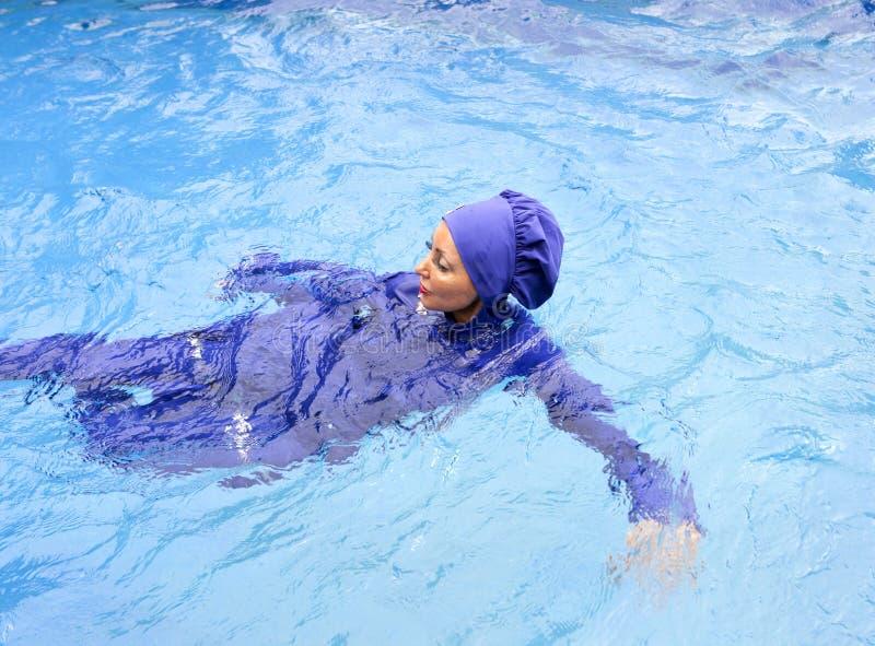 Attractive woman in a Muslim swimwear burkini swims in the pool stock images