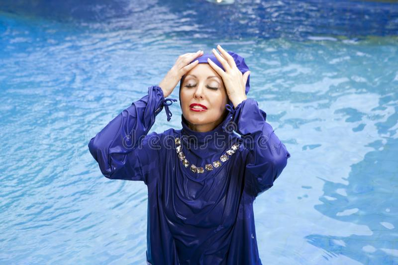 Attractive woman in a Muslim swimwear burkini swims in the pool royalty free stock image