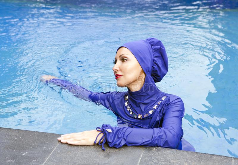 Attractive woman in a Muslim swimwear burkini swims in the pool stock photo