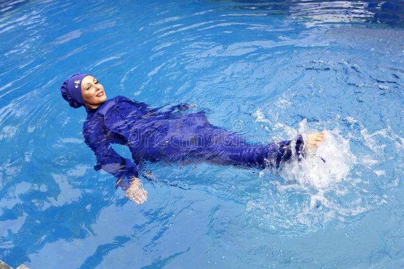 Attractive woman in a Muslim swimwear burkini swims in the pool stock image