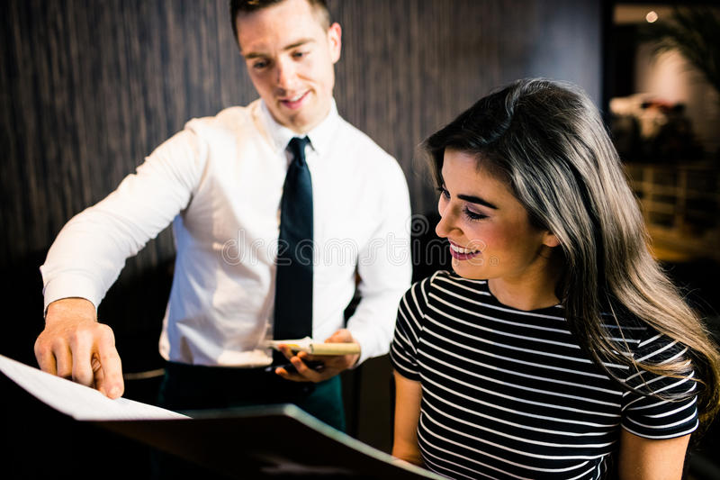 Attractive woman ordering to the waiter from the menu. Attractive women ordering to the waiter from the menu at the restaurant royalty free stock photography