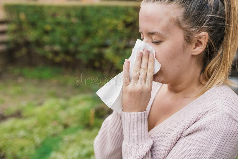Attractive woman outdoor with tissue having allergy. stock photography