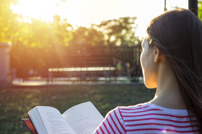 Attractive woman outdoors sitting on a bench reading a book in sunset. Back view royalty free stock photography