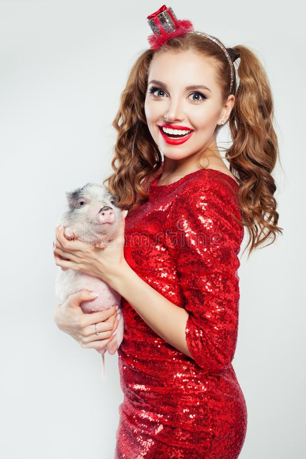 Attractive woman in party dress with cute mini pig and gift hairdecor on white background.  royalty free stock image