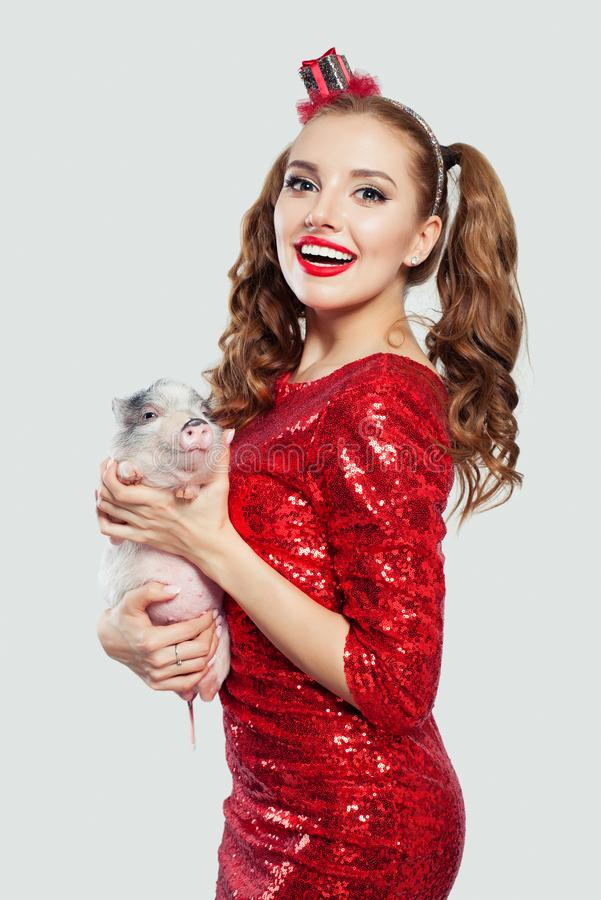Attractive woman in party dress with cute mini pig and gift hairdecor on white background.  royalty free stock photos