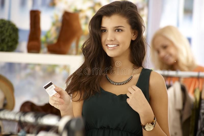 Attractive woman paying by credit card. Attractive female paying by credit card at clothes store, smiling happy stock photo