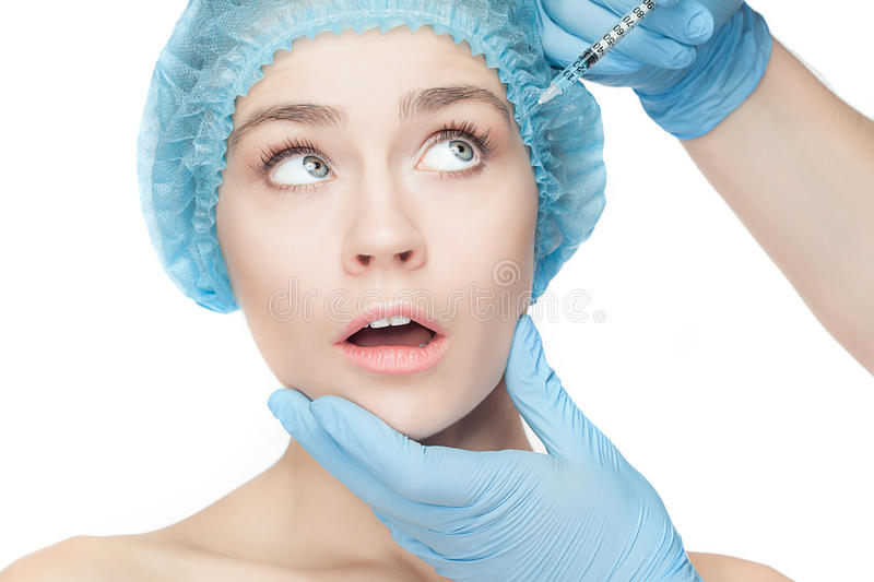 Attractive woman at plastic surgery with syringe in her face stock images