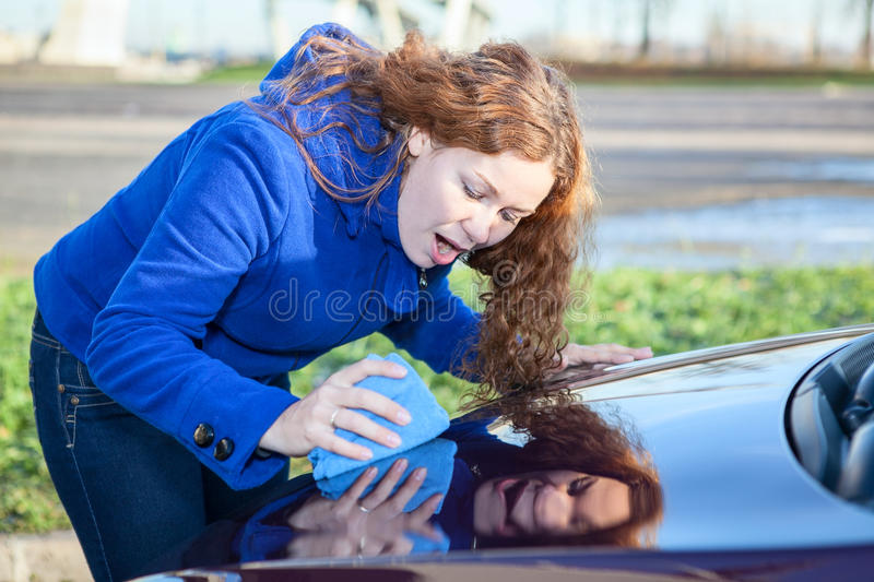 Attractive woman polishing car