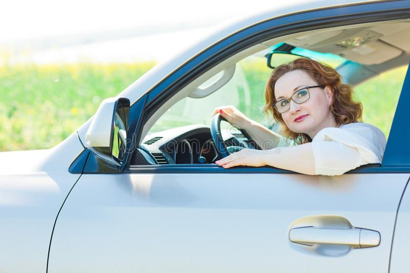 Attractive woman posing in car on drivers seat stock photo
