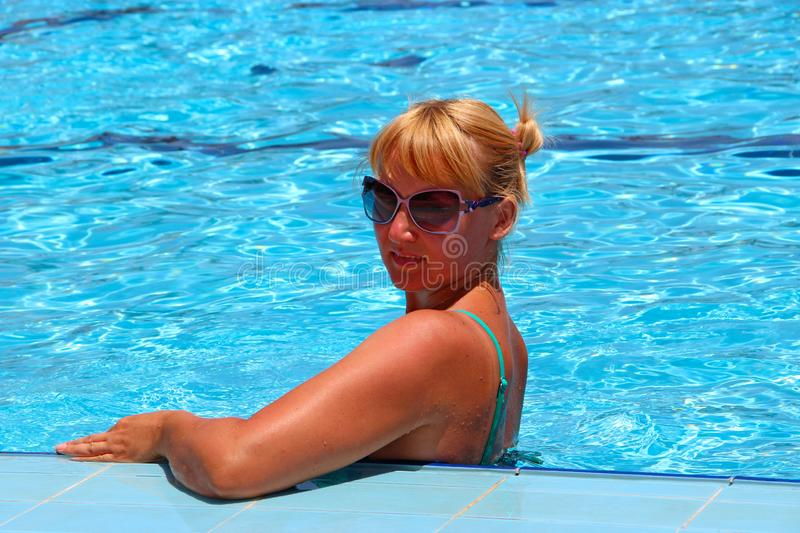 Attractive woman posing during relaxing in swimming pool during vacation royalty free stock images