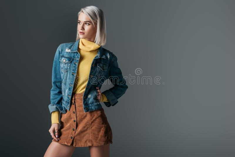 Attractive woman posing in yellow turtleneck trendy corduroy skirt and jeans jacket. Isolated on grey royalty free stock images