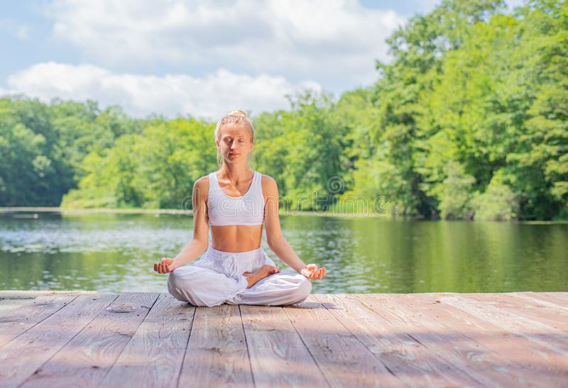 Attractive woman is practicing yoga and meditation, sitting in lotus pose near lake in morning royalty free stock photo