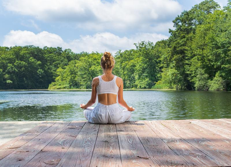 Attractive woman is practicing yoga and meditation, sitting in lotus pose near lake in morning stock photos