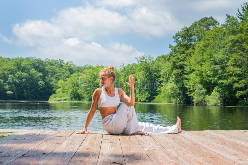 Attractive woman is practicing yoga sitting in Ardha Matsyendrasana pose near lake in morning stock photo