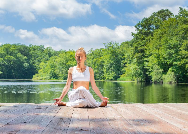 Attractive woman is practicing yoga sitting in Gomukasana exercise near lake. Young woman is meditating in Cow Face pose outdoors royalty free stock photo
