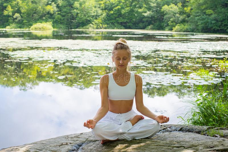 Attractive woman is practicing yoga sitting in lotus pose on stone near lake stock photo