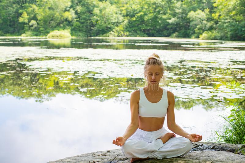 Attractive woman is practicing yoga sitting in lotus pose on stone near lake stock image