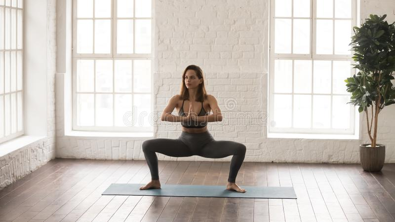 Attractive woman practicing yoga, standing in Sumo Squat, Goddess. Attractive young woman in grey sportswear, leggings and bra practicing yoga at home or in yoga royalty free stock images