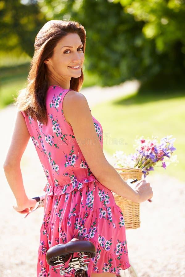Attractive Woman Pushing Bike Along Country Lane stock photos
