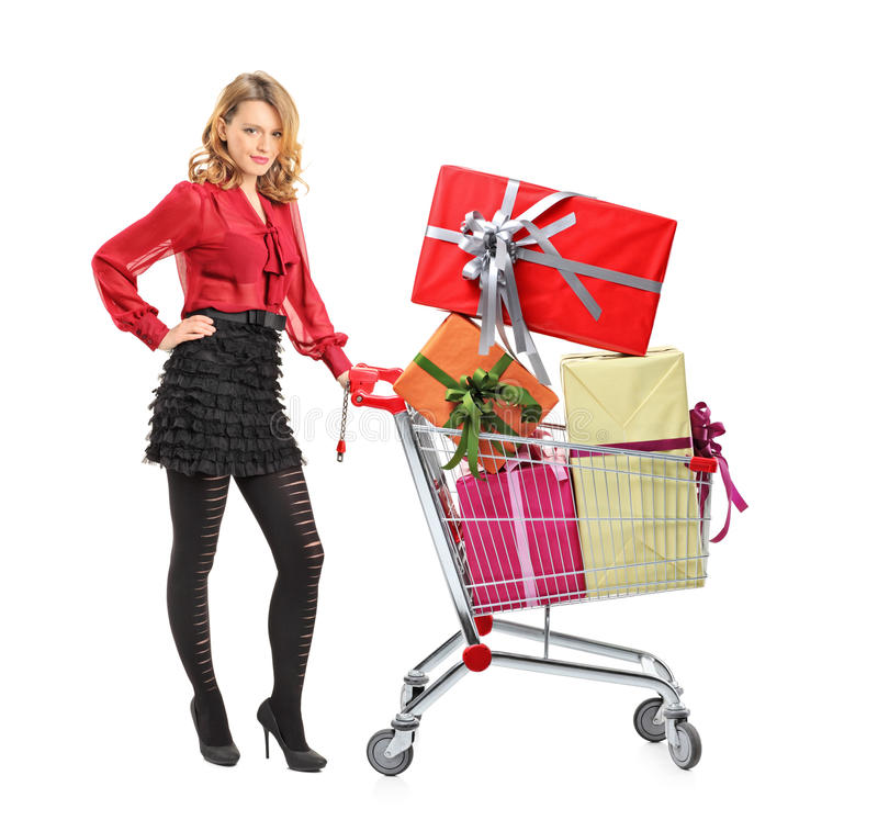 Attractive woman pushing a shopping cart. Full length portrait of an attractive woman pushing a shopping cart full of gifts on white background royalty free stock photography