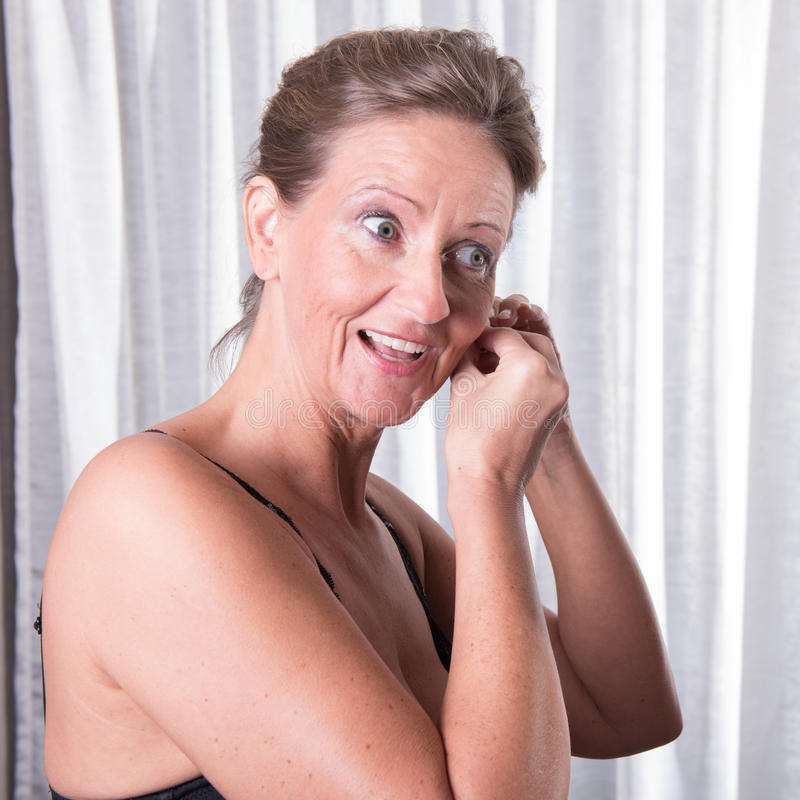 Attractive woman is putting earring on stock photos