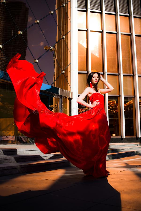 Attractive woman in red fluttered dress. Fire, flame, passion concept. stock photos