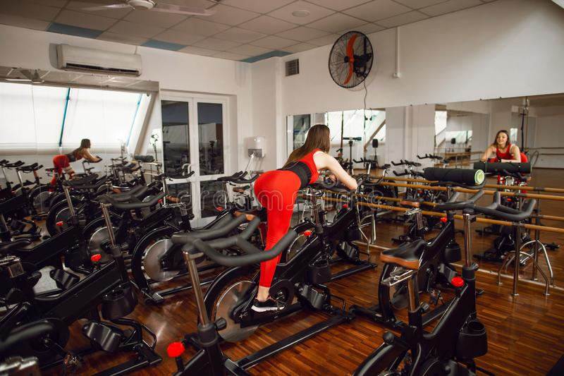Attractive woman in a red sports suit in gym, riding on speed stationary bike. Rear view. Reflection in the mirror. Healthy lifestyle royalty free stock photo