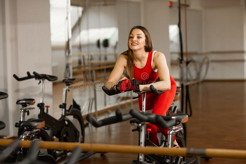 Attractive woman in a red sports suit in gym, riding on speed stationary bike. Reflection in the mirror. Healthy lifestyle royalty free stock image