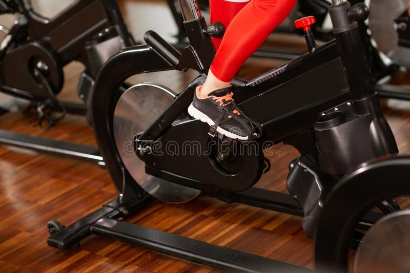 Attractive woman in a red sports suit in gym, riding on speed stationary bike. Women`s legs close up.  royalty free stock photography