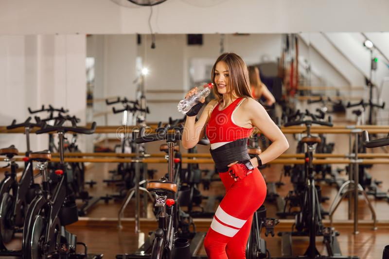 Attractive woman in a red sports suit in gym, standing with a bottle of water near stationary bike. Healthy lifestyle.  stock images