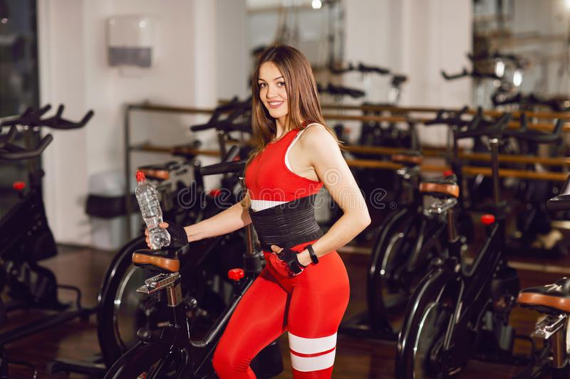 Attractive woman in a red sports suit in gym, standing with a bottle of water near stationary bike. Healthy lifestyle.  stock photography