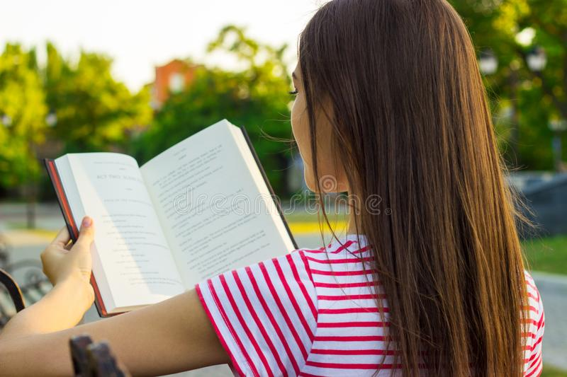 Attractive woman in red and white t-shirt enjoying a book on the bench in the park in summer day. Back view of a young woman readi royalty free stock photos