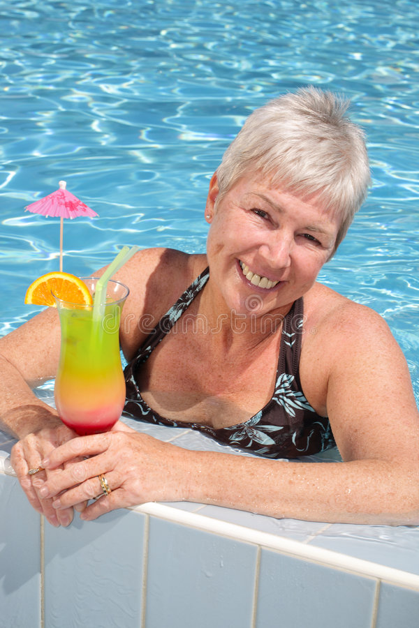 Attractive woman relaxing by the pool stock photo