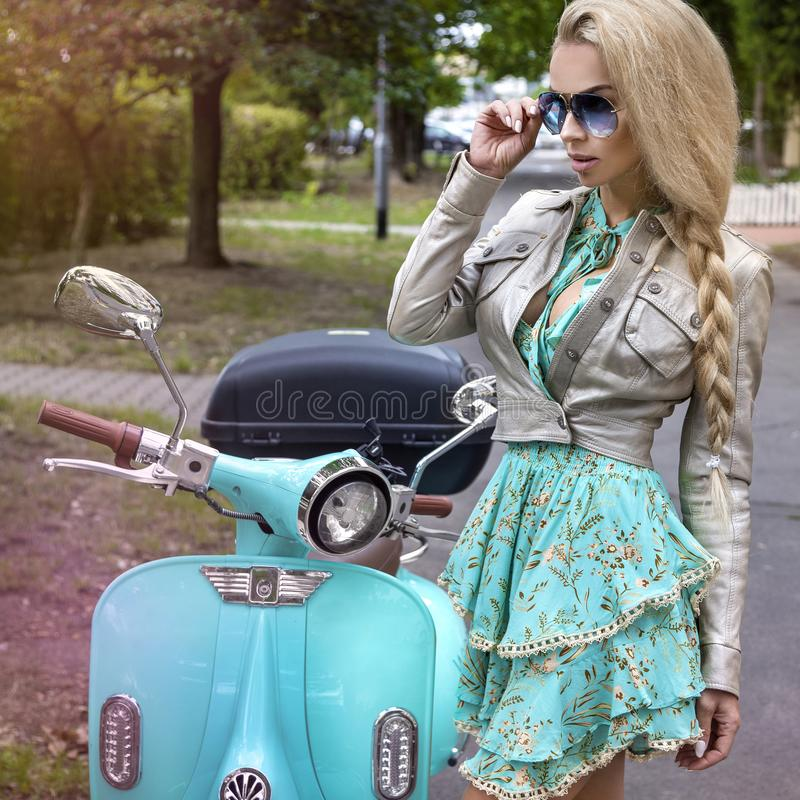 Attractive woman riding on motorbike in street, summer vacation style, traveling, smiling, happy, having fun, stylish outfit, stock photo