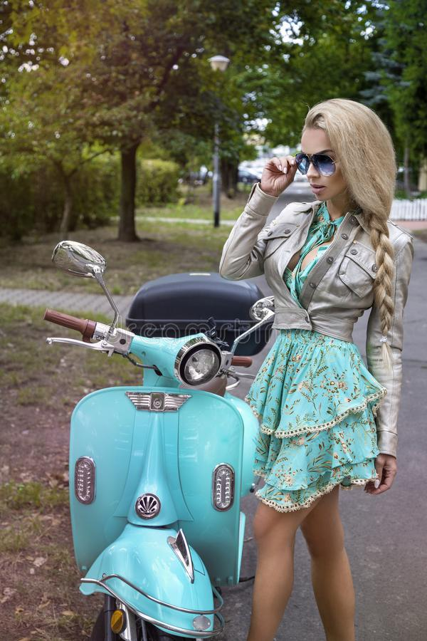 Attractive woman riding on motorbike in street, summer vacation style, traveling, smiling, happy, having fun, stylish outfit, royalty free stock image