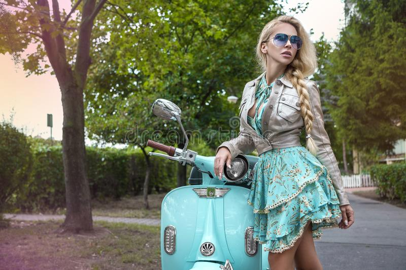 Attractive woman riding on motorbike in street, summer vacation style, traveling, smiling, happy, having fun, stylish outfit, royalty free stock photo